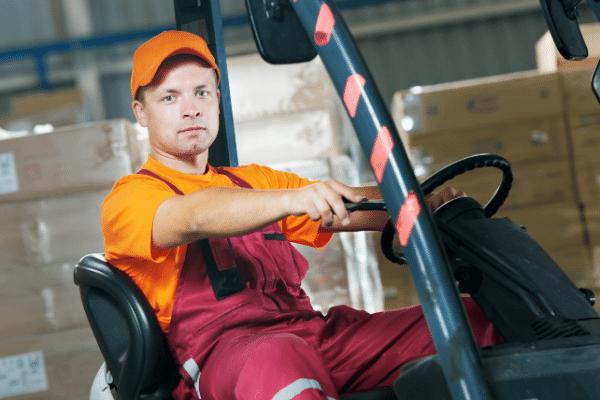 עובד יושב במלגזה שבמחסן